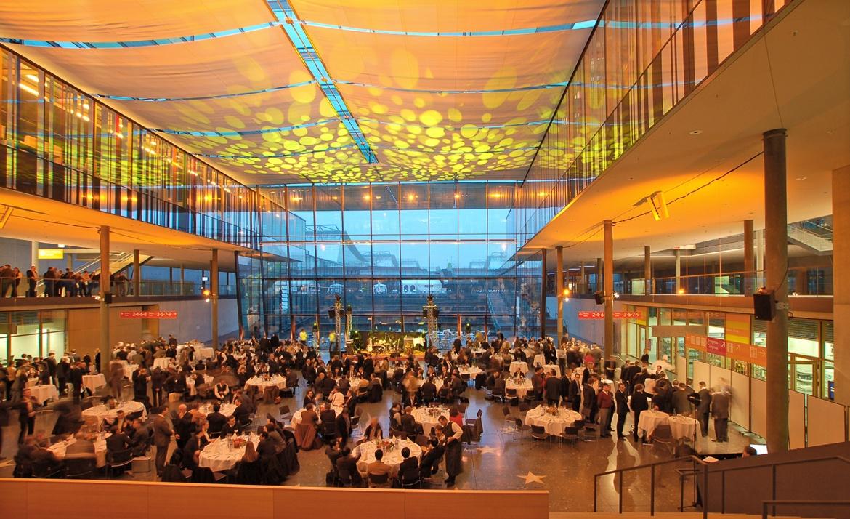 Blick in das Foyer bei der Abendveranstaltung. Die Gäste sitzen an runden, hübsch gedeckten Tischen beim Essen.