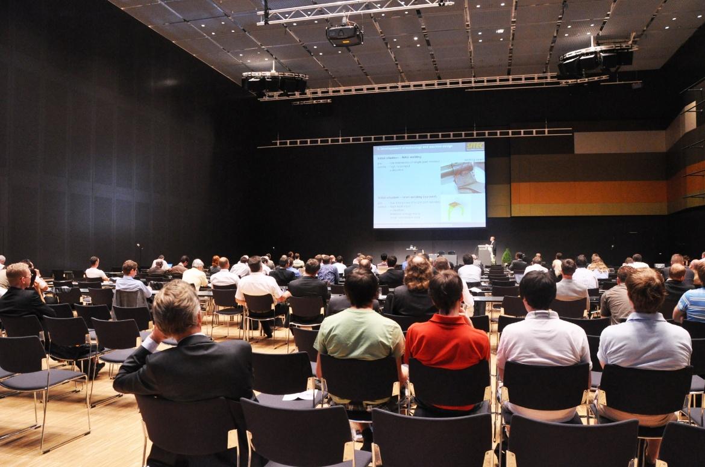Das Foto zeigt von hinten die Konferenzteilnehmer, wie sie einem Vortrag lauschen. Im Hintergrund sieht man auf der Bühne eine große Leinwand mit einer Präsentation.