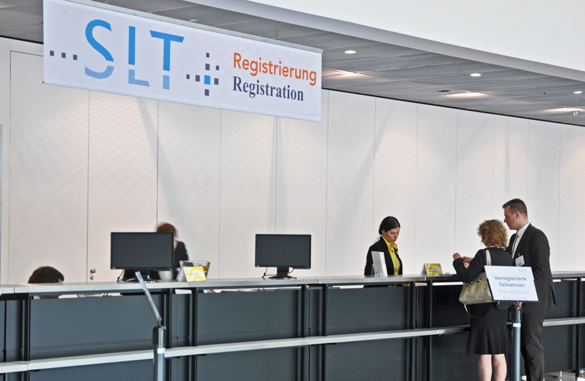 The photo shows the registration desk where 2 people are currently registering for the conference.